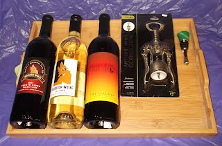 Wine gift basket with 3 bottles of wine, cockscrew, wine bottle sopper, and wooden tray