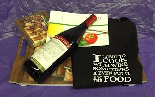 Wine gift basket with bottle of wine, apron, tray, napkins, and cookbook.